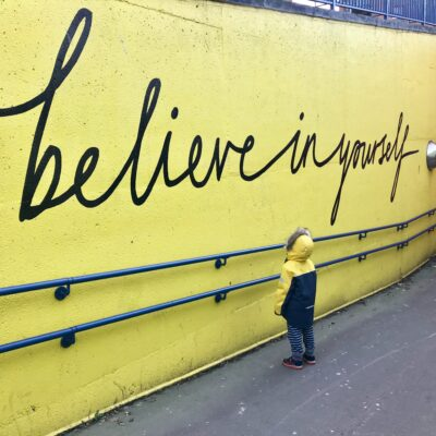 a little boy staring at graffiti that says believe in yourself