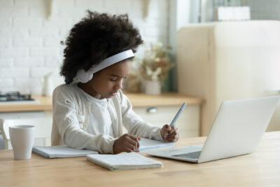 African schoolgirl in headphones using laptop do homework at home