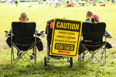 People sitting in chairs with stay calm sign
