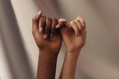 women holding pinkies as friends